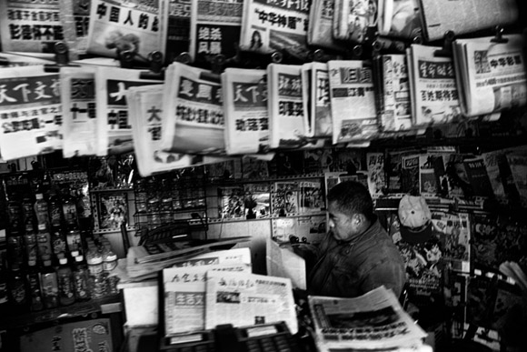 A newspaper seller sits inside a newsstand kiosk reading a newspaper in Kunming, Yunnan Province, China.