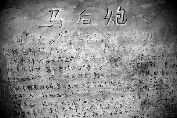 A handwritten message meaning something like Too little, too late remains in protest on the side of a building marked for demolition in central Kunming, Yunnan Province, China.