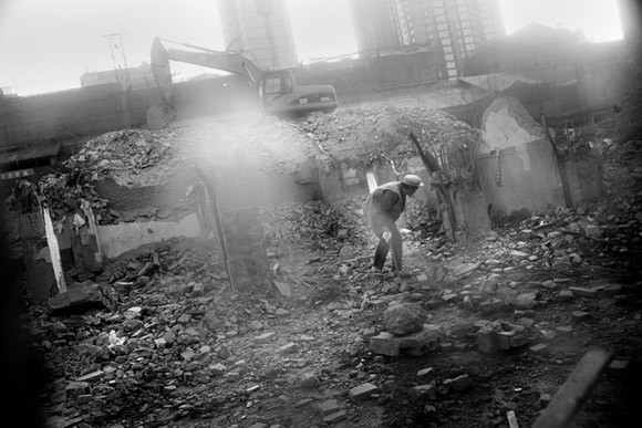 Workers salvage rebar and other reusable materials from the site of former houses in an old neighborhood in Kunming, Yunnan, China.