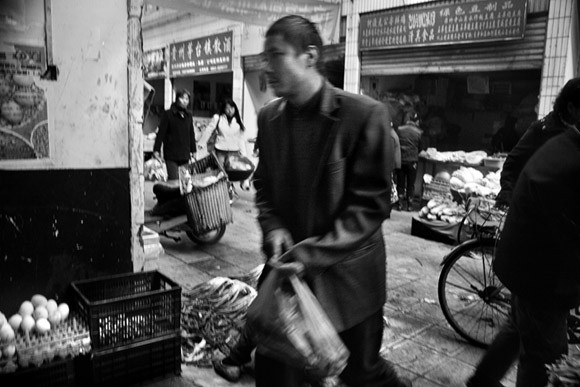 Shoppers walk among the stalls in a large outdoor market in central Kunming, Yunnan Province, China.