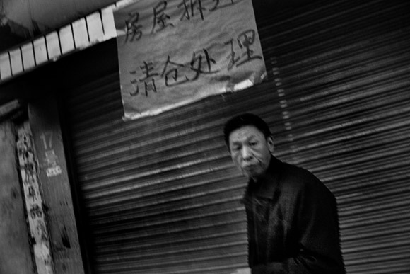 A man walks past a closed shop in an old neighborhood marked for demolition in Kunming, Yunnan, China.