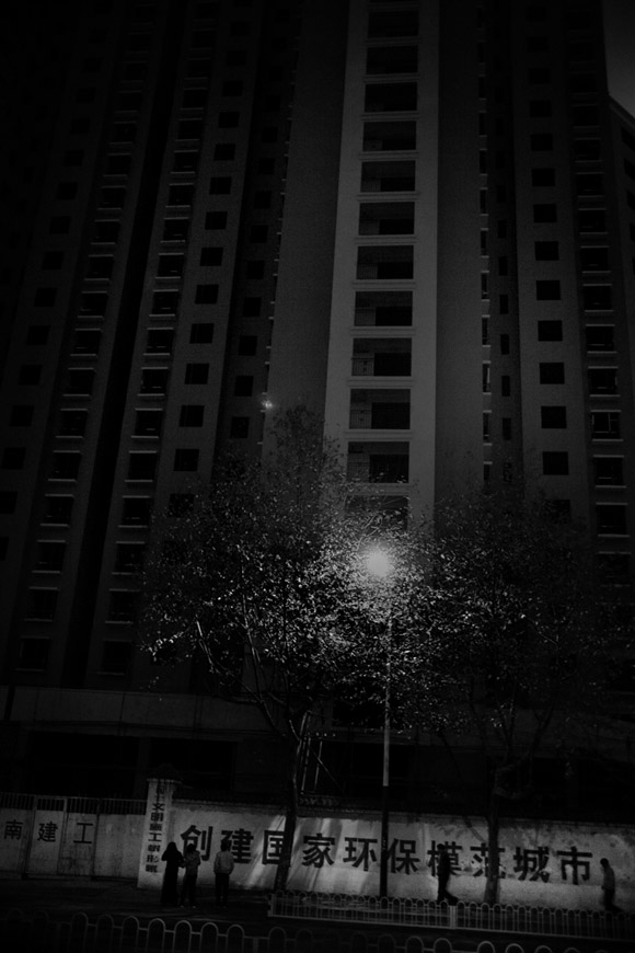Pedestrians walk past unfinished high-rise apartment buildings at night in Kunming, Yunnan Province, China.