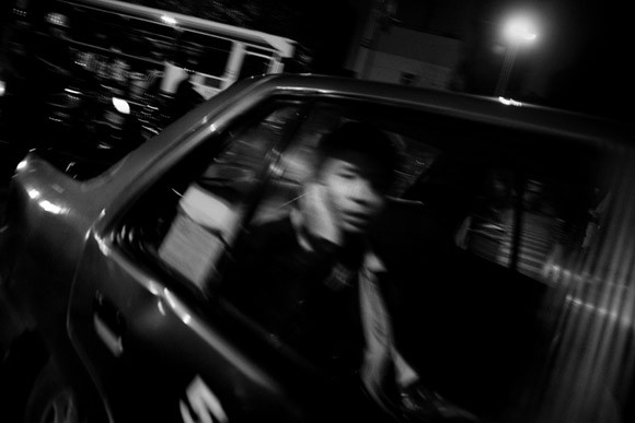 A man talks on a cell phone while riding in a taxi in central Kunming, Yunnan Province, China.