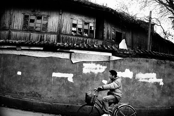 A bicyclist rides past partially-demolished old-style buildings in central Kunming, Yunnan Province, China.