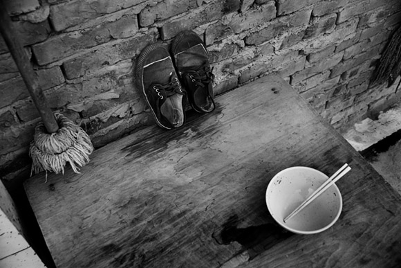 Workers' shoes, an empty food bowl, and a well-used map sit on a table in a partially-demolished old neighborhood in central Kunming, Yunnan Province, China.