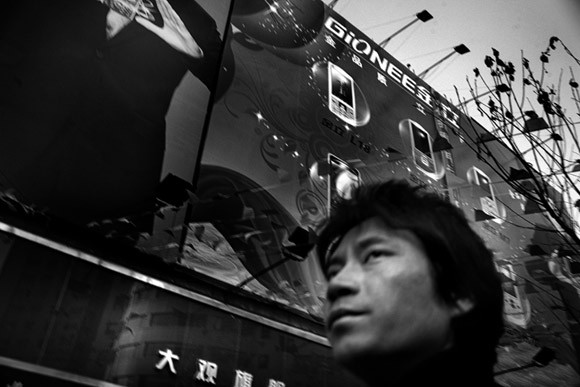 A man walks past a cell phone advertisement in the central shopping area of Kunming, Yunnan Province, China.