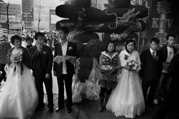 Brides and grooms stand outside of a wedding reception in central Kunming, Yunnan Province, China.