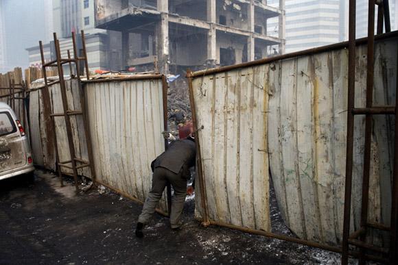 Construction workers enter a work site in Urumqi, Xinjiang, China.
