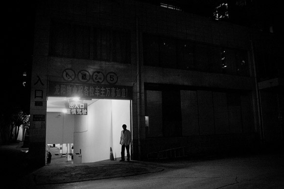 A parking garage attendant stands outside of the entryway in Kunming, Yunnan Province, China.