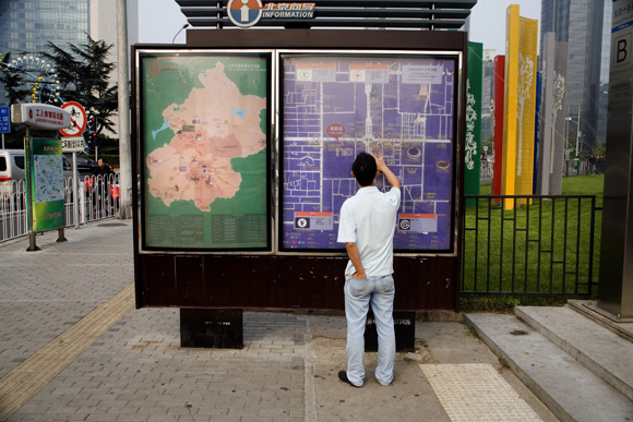 A man looks at a city map in the Chaoyang area of Beijing, China.