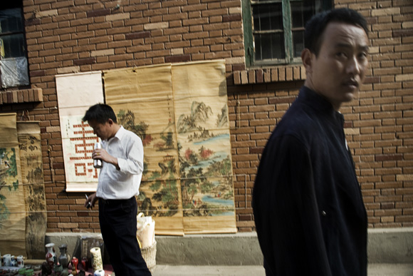 Men stand next to a brick wall in the antique market in Tianjin, China.