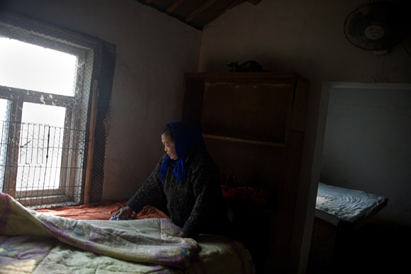 A caretaker tends the bedding provided for cats in a small farmhouse at Ha Wenjin's no-kill dog and cat rescue farm outside Nanjing, Jiangsu, China.