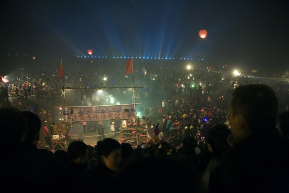 Crowds gather to watch fireworks and lanterns lift into the sky above the frozen Songhua River during Lantern Festival celebrations in central Haerbin, Heilongjiang Province, China.