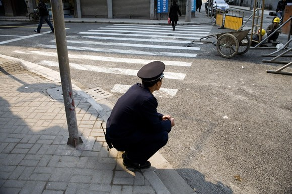 A security guard squats on a sidewalk looking over a street in Shanghai, China.