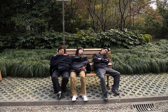People sleep on a bench in People's Park in central Shanghai, China.