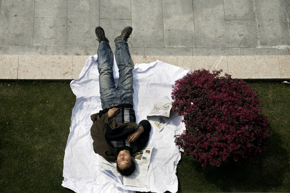 A man sleeps on grass in People's Park in central Shanghai, China.  People's Park is known as Renmin Park or Renmin Guangchang in Mandarin chinese.