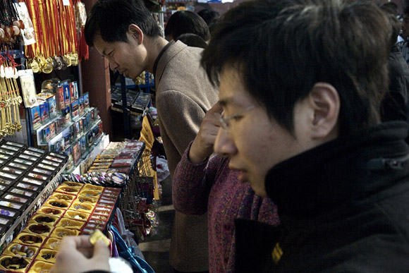 Tourists shop for souvenirs outside the Forbidden City in Beijing, China.
