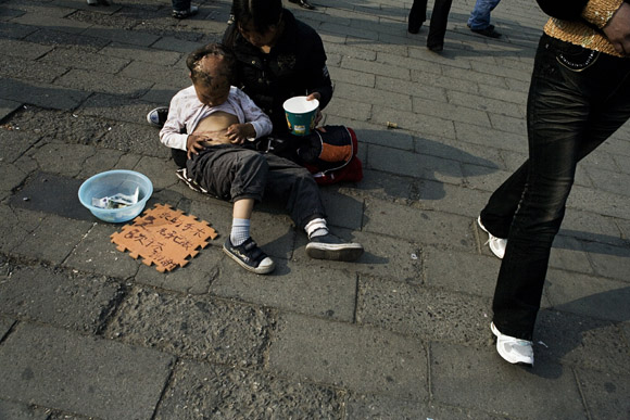 A woman and a deformed child beg for change in the Forbidden City in Beijing, China.