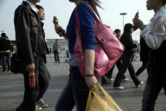 Tourists walk around the north end of Tiananmen Square near the Forbidden City in Beijing, China.