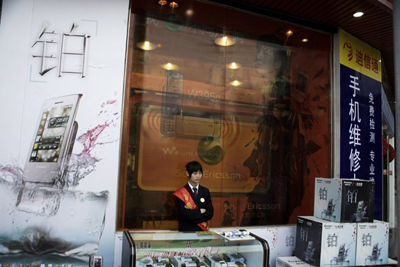 A cell phone sales clerk stands outside a shop to attract passers-by in the Bund area of Shanghai, China.