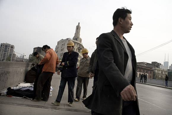 Construction workers walk past street vendors on a bridge in the Bund area of central Shanghai, China.