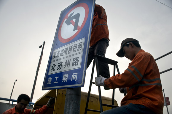 A work crew installs a new roadsign in the Bund area of central Shanghai, China.