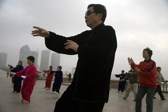 Elderly people practice tai chi on the boardwalk in Huangpu Park on the waterfront in the Bund in Shanghai, China.