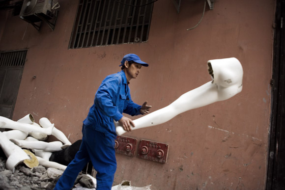 A worker throws away discarded and broken mannequins in an alley of Nanjing East Road in the Bund in Shanghai, China.