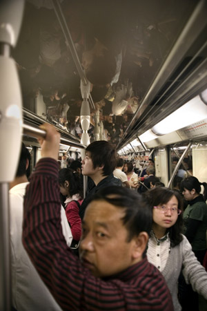 People ride in a crowded subway car in Shanghai, China.