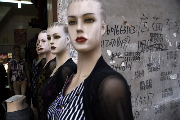 Mannequins stand outside a tailor's shop in Shanghai, China.