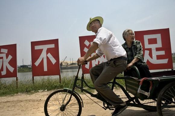 A couple rides along a river outside Jiangning, Jiangsu Province, China.