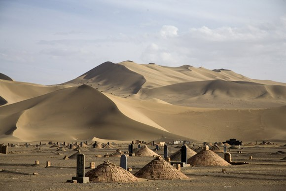 A cemetery stands beneath dunes of the Gobi Desert near Dunhuang, Gansu, China.  An area of the desert near this dune will be the site of the world's largest solar power generating field. The desert and surrounding areas is closely protected and managed by the local government, but ethnic groups have been given special permission to use the desert according to their traditions.