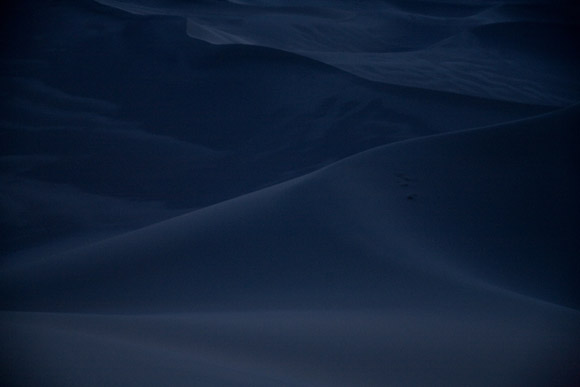 The moon illuminates the dunes of the Gobi Desert at night near Dunhuang, Gansu, China.  An area of the desert near this dune will be the site of the world's largest solar power generating field.