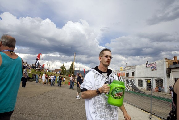 A man walks with a large Mountain Dew mug in Butte, Montana, USA.