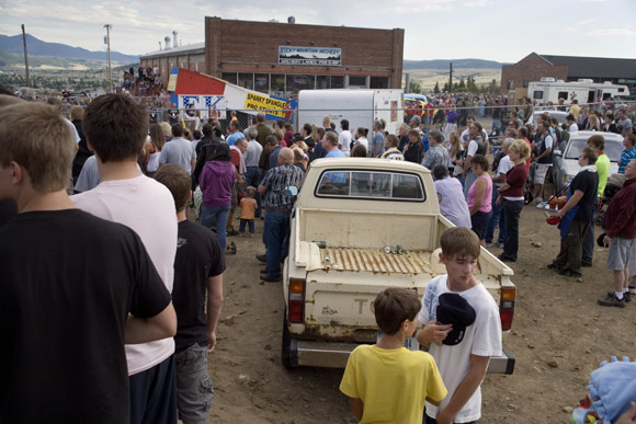 The crowd listens to the National Anthem before Spanky Spangler's daredevil car jump stunt at the end of Evel Knievel Days in Butte, Montana, USA.