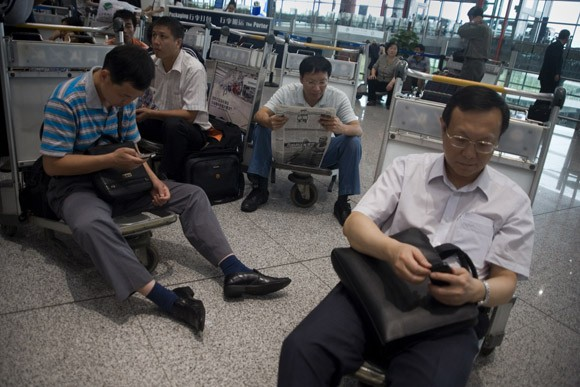 Stranded travelers wait for news about delayed and canceled flights at Beijing Capitol Airport's Terminal 3 in Beijing, China, on 17 June 2010.  Almost all departures and many arrivals were severely delayed or canceled due to thunderstorms and hail in the area.