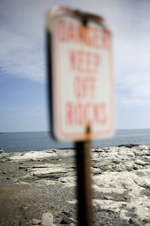 "A sign warns ""Danger Keep Off Rocks"" at Ocean Drive State Park in Newport, Rhode Island, USA."