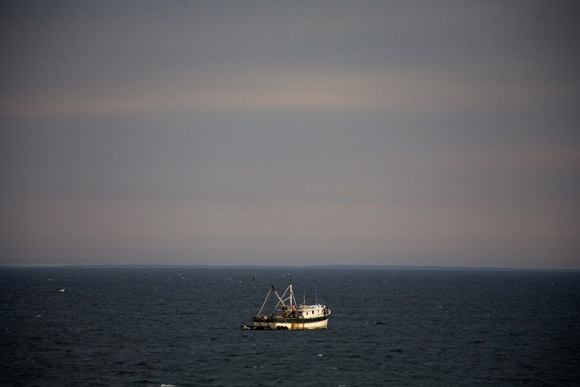 A fishing boat floats in Cape Cod Bay near Provincetown, Massachusetts, USA.