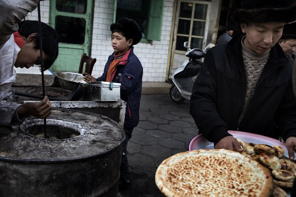 Uighur men bake flat bread (nan) in a barrel oven in the Old City section of Kashgar, Xinjiang, China.