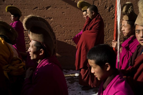 Tibetan Buddhist Monks of the Gelugpa Order (Yellow Hat Sect) accompany a thangka (painting of Buddha) through the streets of Xiahe, Gansu Province, China, during the Monlam Festival at the Labrang Monastery. Monks work on the painting for the year preceding the festival and then display it on a nearby hillside for about an hour.