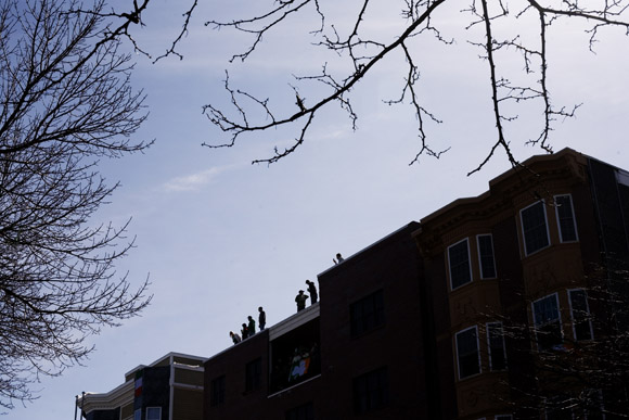 People watch the St. Patrick's Day Parade from building rooftops in South Boston, Massachusetts.